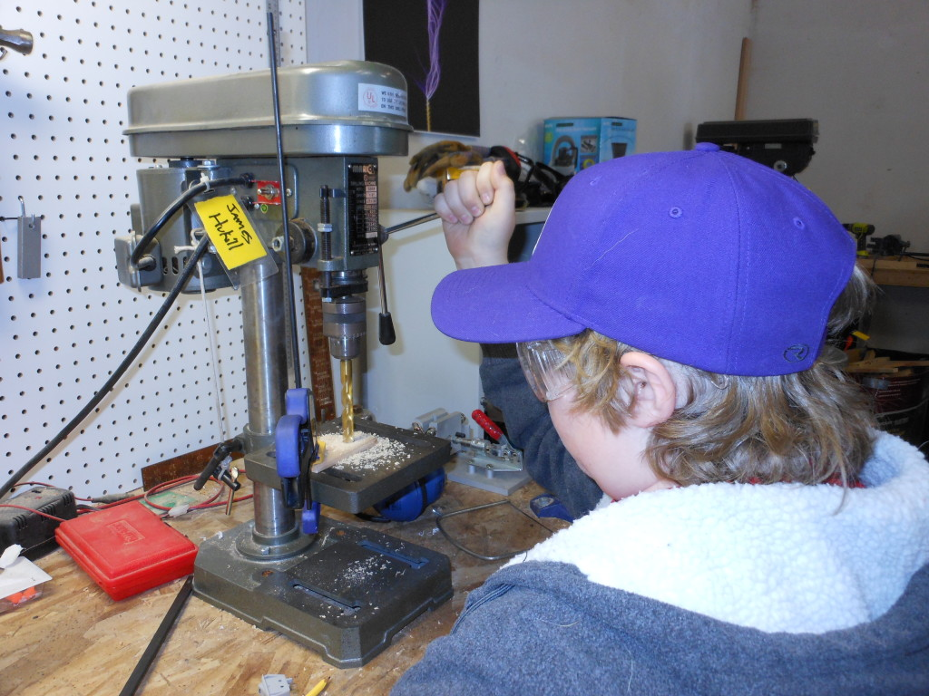 Quinn learns to use the drill press